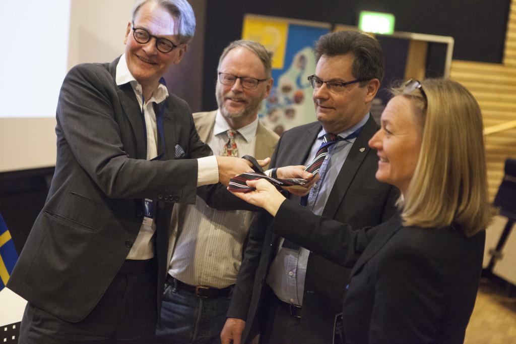 Carl Rosén från Näringsdepartementet inviger företagsklustret genom att klippa av slipsarna för Olle Persson, ansvarig för klustret norra noden, Göran Berlemo, VD för Aerospace Cluster Sweden. Till höger i bilden är Johanna Bergström-Roos, arrangör av Space Innovation Forum. Att klippa slipsar är en gammal rymdtradition från raketbasen Esrange i Kiruna som symboliserar en mindre formell approach där fokus läggs på arbete och nytta i stället för långa möten.